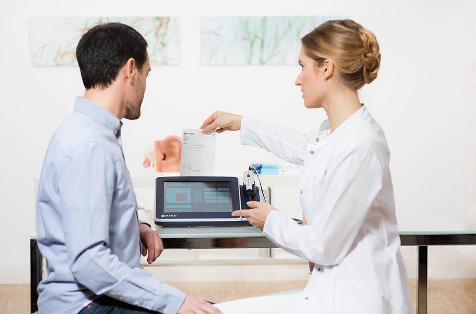 Audiologin erklärt Patient Messergebnisse auf dem Bildschirm des MAICO Tympanometers