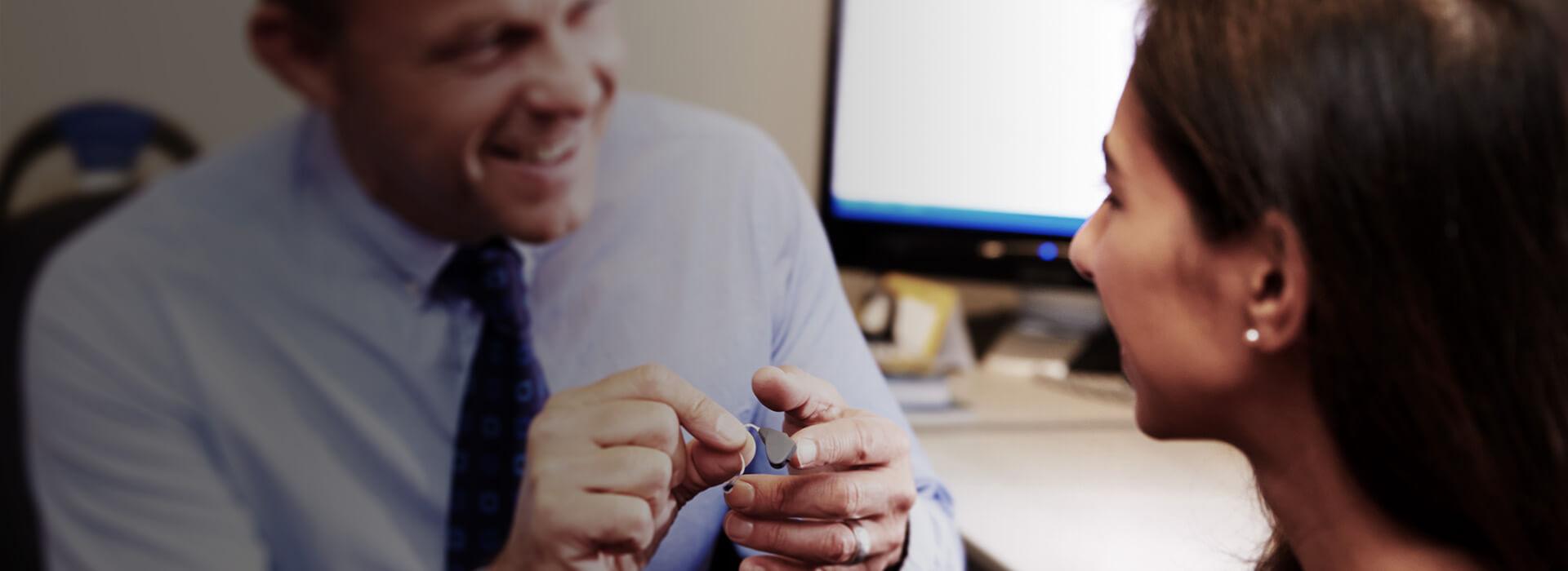 Un audioprotesista mostra ad una giovane donna l'apparecchio acustico