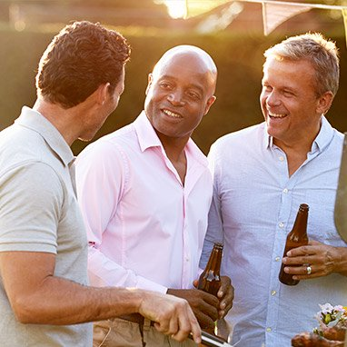 Tre uomini che ridono al barbecue