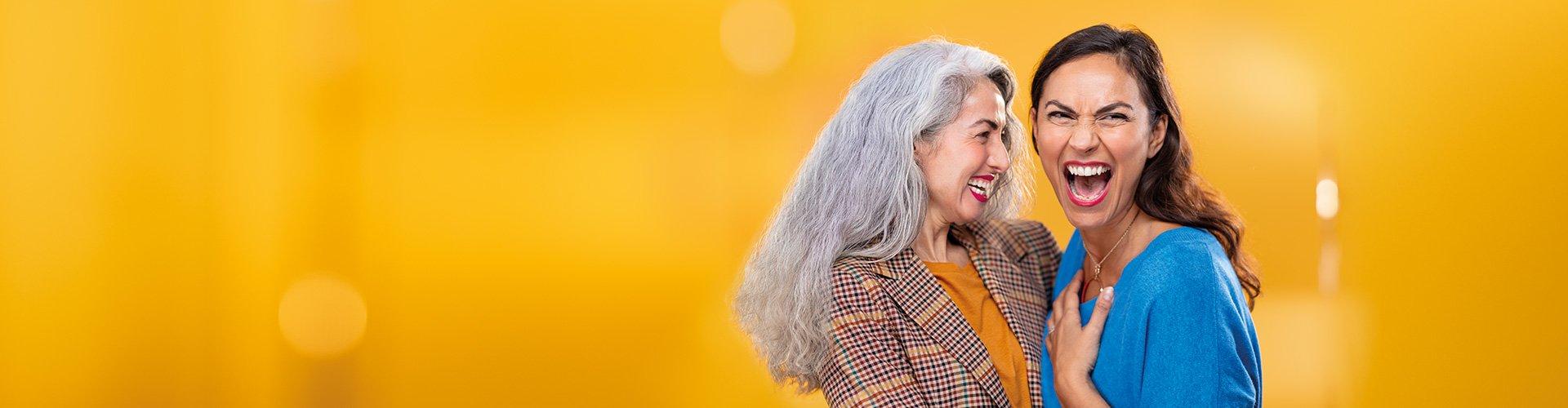 2人の中年の女性がお互いをハグします。 1つは、フィリップスHearLinkインイヤーイヤー補聴器を着用しています。