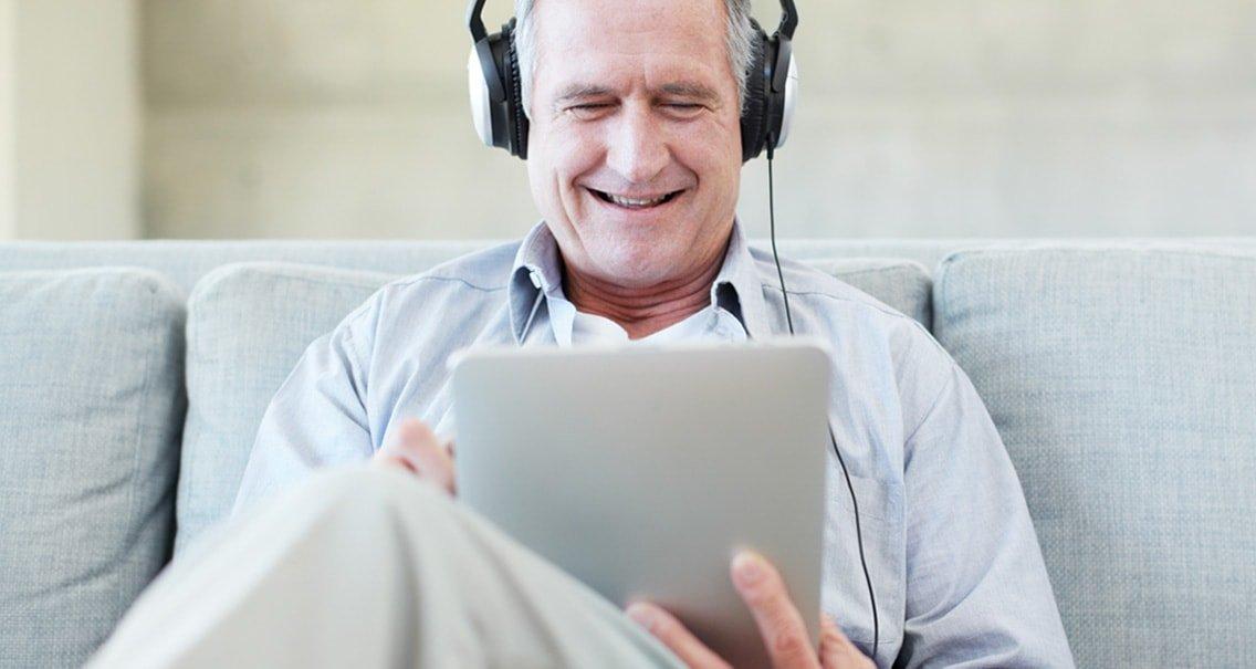 ソファに座り、自身の聞こえの状態をオンライン聞こえのチェックを使ってチェックしようとしている男性。