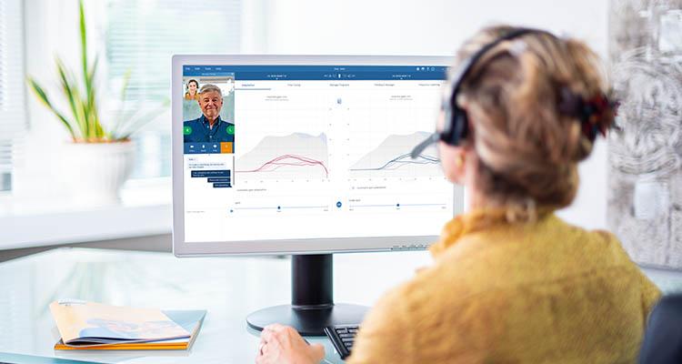 フィリップス ヒアリンク補聴器のユーザーと、オンライン リモートフィッティングに映る補聴器専門家。