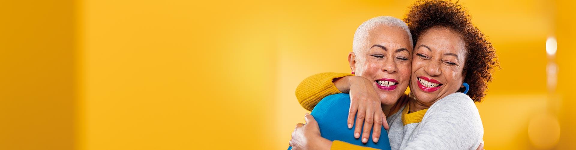 중년 여성 두 명이 서로 포옹합니다. 한 명은 Philips HearLink 귀걸이형 보청기를 끼고 있습니다.