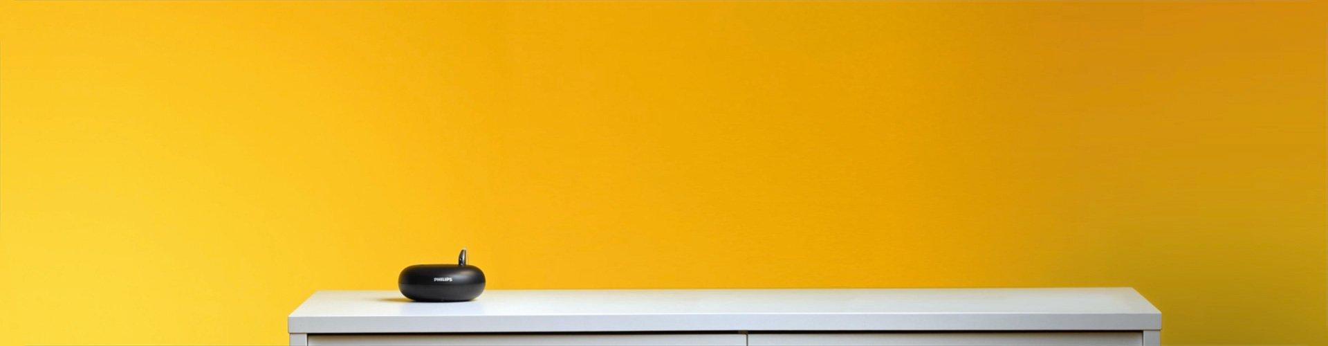 필립스 히어링크 충전형 보청기를 충전기에 놓는 남자. 3시간 충전으로 하루 종일 사용하세요.