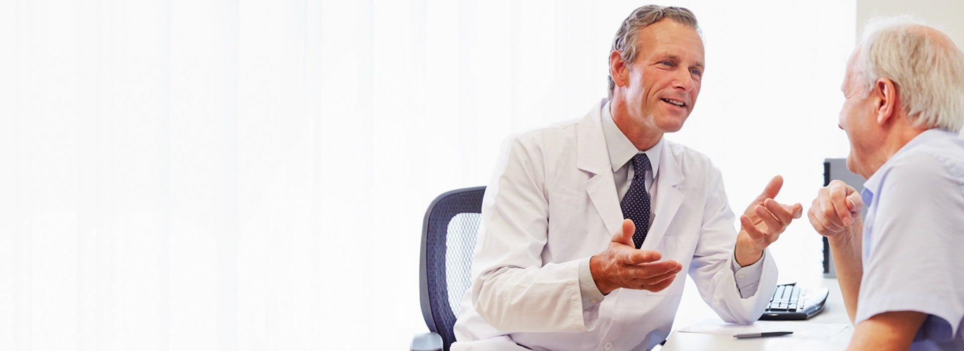 Vyras konsultacijoje pas klausos specialistą arba audiologą.
