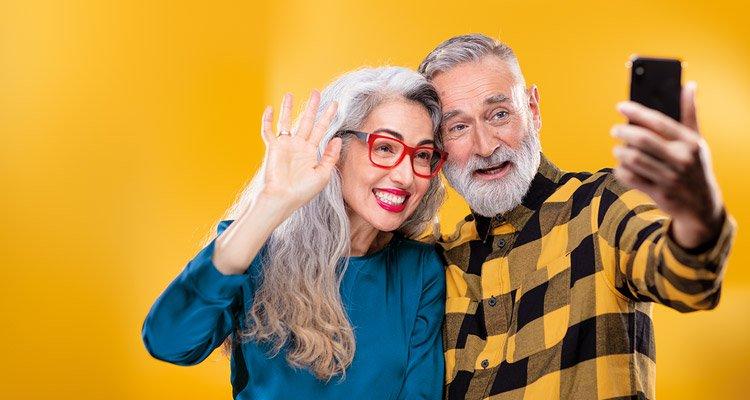 Vrienden van middelbare leeftijd gebruiken een smartphone om te verbinden met familie en vrienden door het houden van een videogesprek