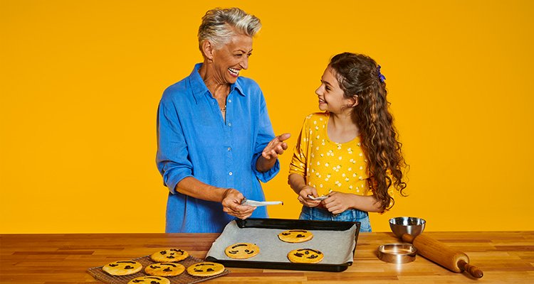 Een oma die Philips HearLink draagt en koekjes aan het bakken is met haar kleinkind.