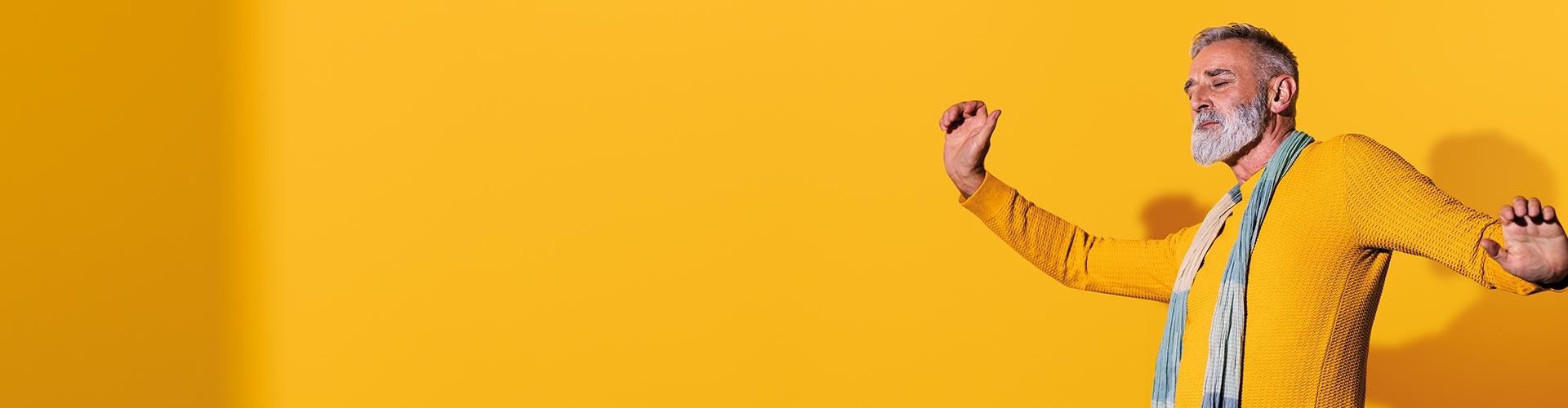 Tańczący mężczyzna w średnim wieku noszący aparaty słuchowe Philips HearLink i okazujący pewność siebie.