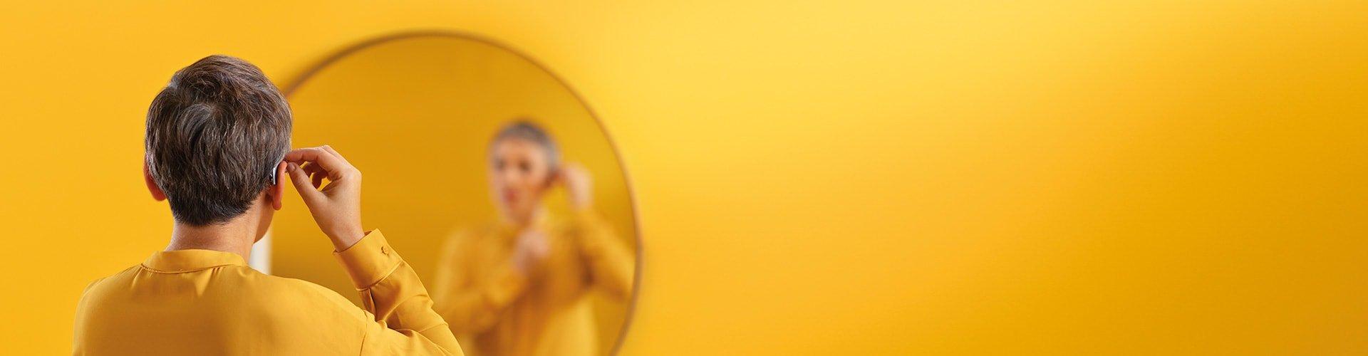 Kobieta zakłada swój aparat słuchowy Philips. Aparaty Philips HearLink dostępne są w szerokiej gamie modeli.