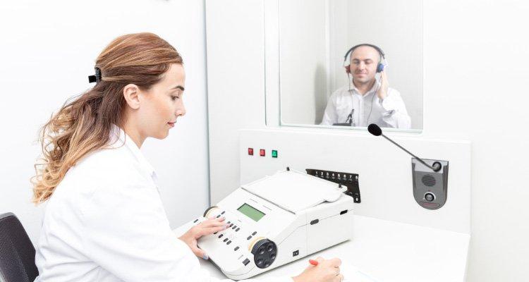 Protetyk słuchu przeprowadzający badanie słuchu. Protetyk wyjaśnia, który aparat będzie najlepszy i omawia ceny.