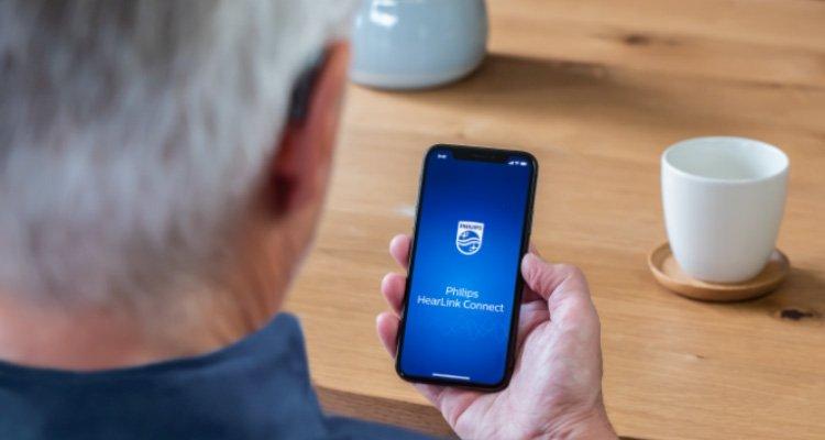 Użytkownik aparatu słuchowego Philips otwierający aplikację Philips HearLink Connect, aby wziąć udział w sesji Remote Fitting.