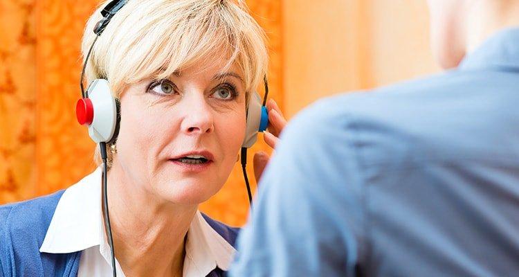 Senhora fazendo avaliação auditiva com um fonoaudiólogo.