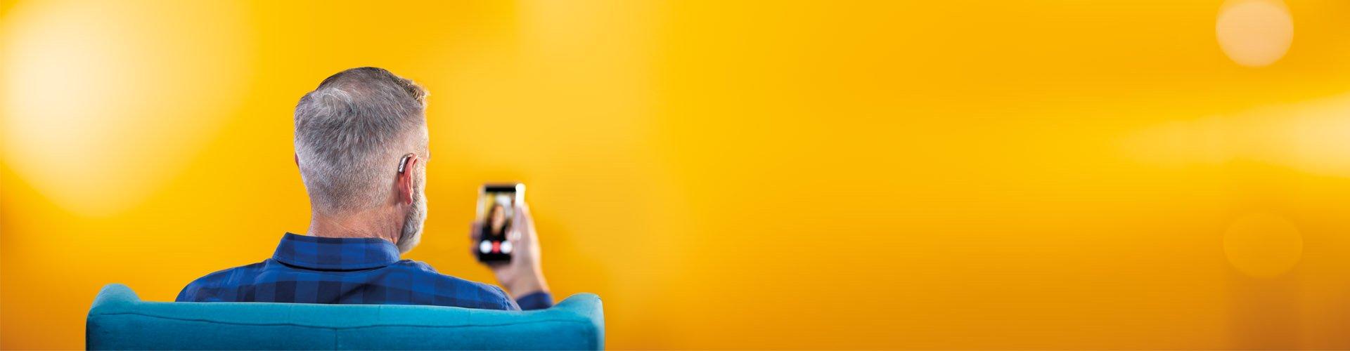 Homem de meia idade a usar um smartphone e os seus aparelhos auditivos Philips HearLink para se ligar à família e amigos através de uma vídeo-chamada.