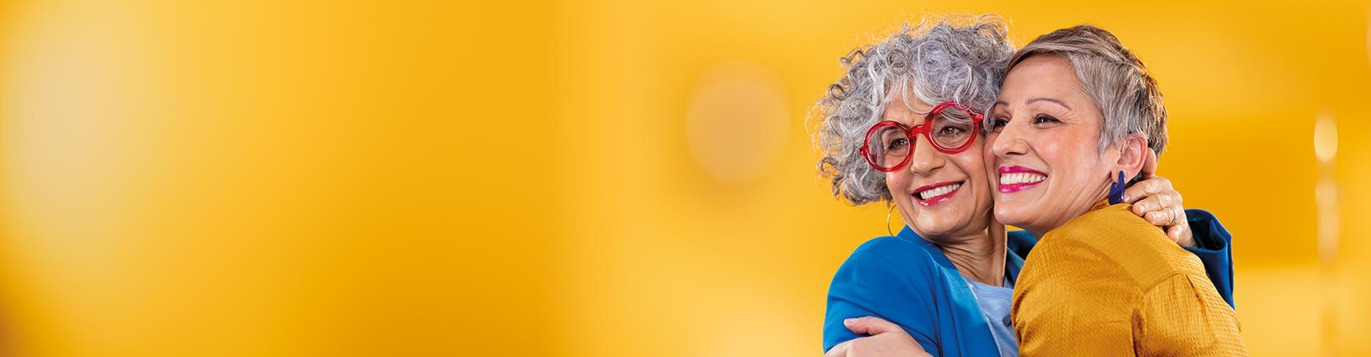 İki orta yaşlı kadın birbirlerine sarılıyor. Biri Philips HearLink neredeyse görünmez kulak içi işitme cihazları kullanıyor.