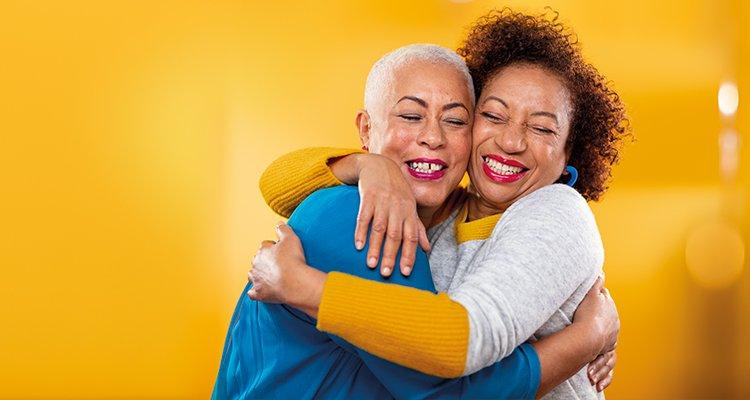 İki orta yaşlı kadın birbirlerine sarılıyor. Kadınlardan biri Philips HearLink kulak arkası işitme cihazları takıyor.