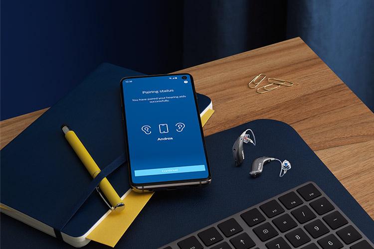 Philips HearLink miniRITE T R işitme cihazları, Philips HearLink uygulaması açıkken bir akıllı telefonun yanında.