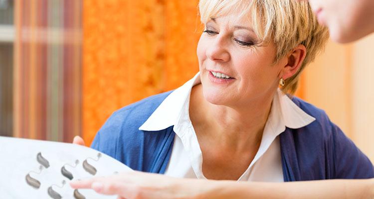 İlgili bir müşteriye danışmanlık yaparken farklı işitme cihazı seçeneklerini gösteren bir işitme uzmanı