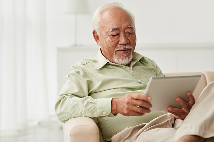 Man sitting on a couch looking on his iPad for Philips HearLink compatibility