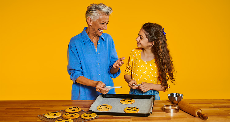 奶奶配戴著飛利浦助聽器與孫女一同烤餅乾