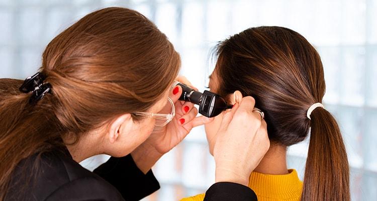 一位聽力照顧專家正在使用耳鏡檢查患者的耳道
